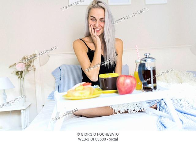 Smiling young woman having breakfast in bed