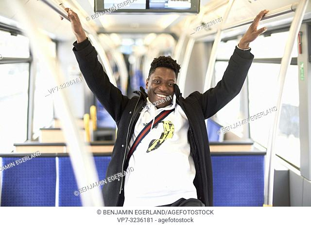 young smiling man in tram, public transport, in Munich, Germany