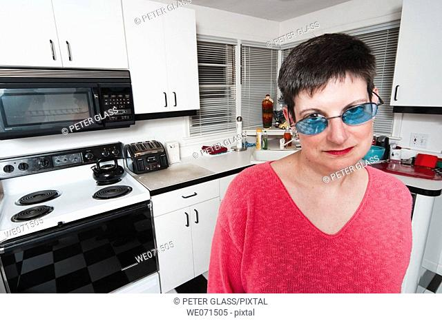 Woman, wearing sunglasses, posing in her kitchen
