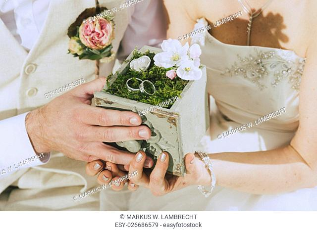 detail shot of a beautifully decorated wooden box with moss and two wedding rings held by hands. In the background one sees bride and groom