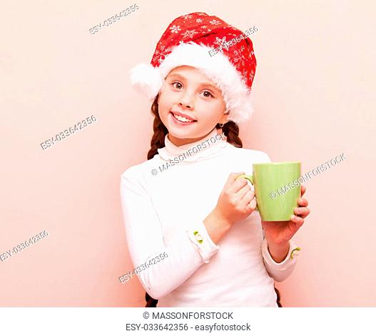 Portrait of a young girl with cup and Santa Claus hat on pink background