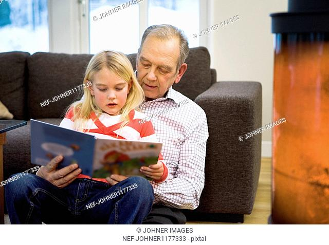 Grandfather reading to girl