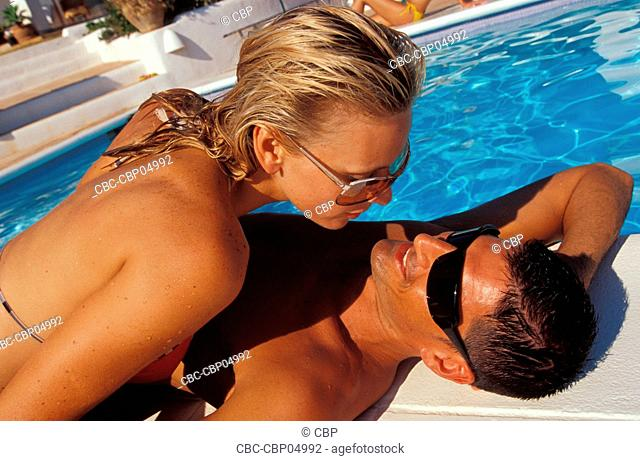 Young Couple Lying Out By Pool