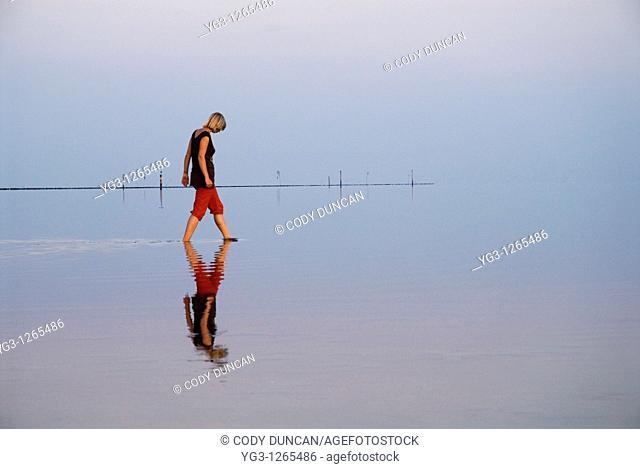 Reflection of woman walking in Wadden sea, Juist, Germany