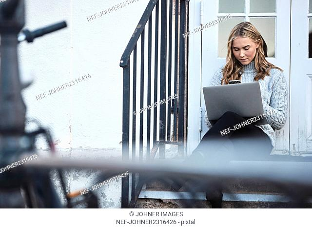 Woman using smartphone on front stoop