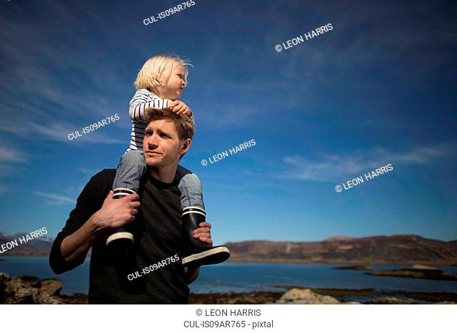 Father carrying son on shoulders, Loch Eishort, Isle of Skye, Hebrides, Scotland