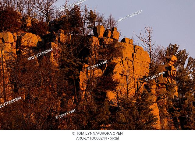 The morning sun reflects off of the rock face above Devil's Lake in central Wisconsin