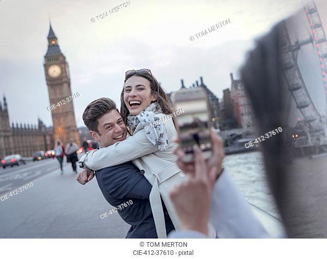 Playful couple tourists being photographed on bridge near Big Ben, London, UK