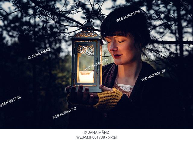 Portrait of woman with closed eyes holding storm lamp