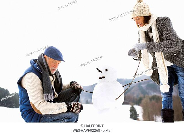 Senior couple building up snowman in winter