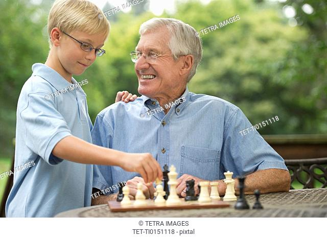 Grandfather and grandson 10-11 playing chess on porch