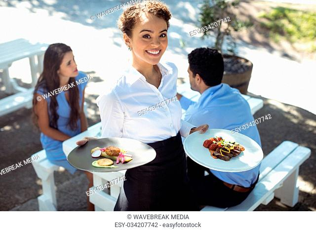 Smiling waitress holding delicious food in kitchen