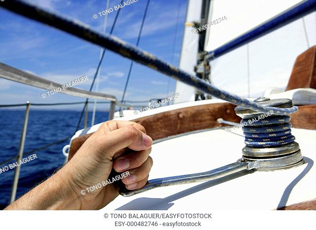 Blue summer water and sky in a sailboat race, sailor man in winch