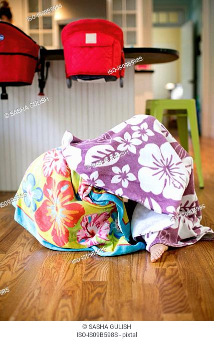 Toddler hiding under blanket and another in baby chair in kitchen