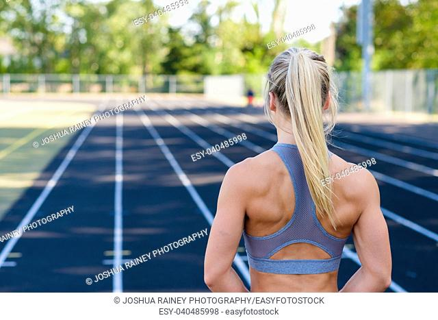 Muscular female athlete looking towards her lane while working out on an outdoor track in the summer