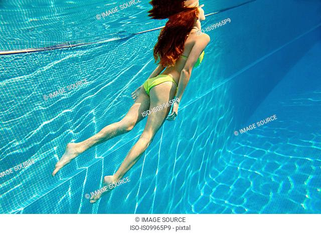 Young woman swimming underwater in swimming pool