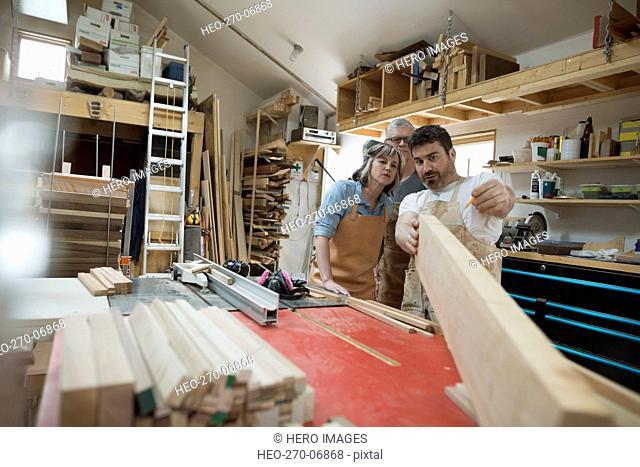 Carpenters examining wood plank in workshop