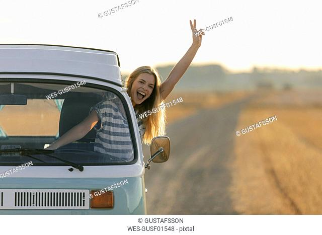 Excited young woman making victory hand sign out of camper van window in rural landscape