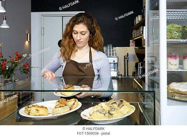 Close-up of young woman serving cinnamon rolls at cafe