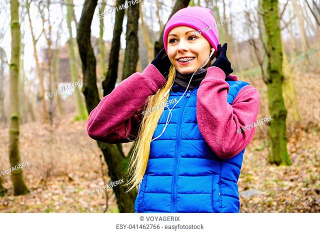 Sports and activities in cold time. Slim fit fitness woman outdoor. Athlete teen girl wearing warm sporty clothes outside listening to music