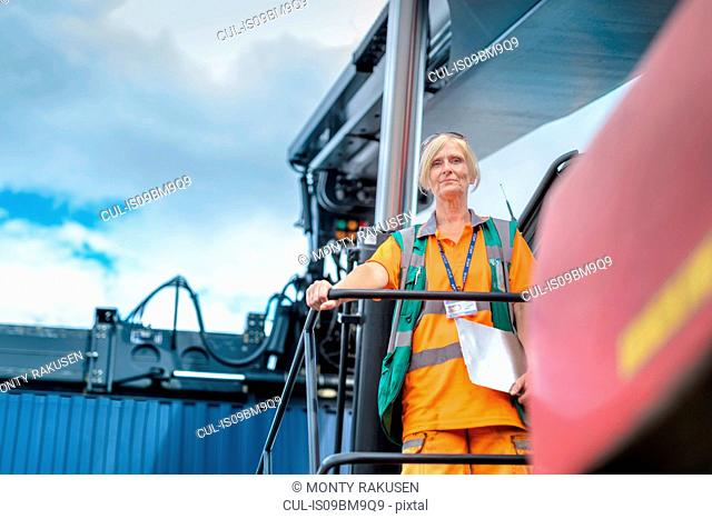 Portrait of female container lift operator with shipping container in port