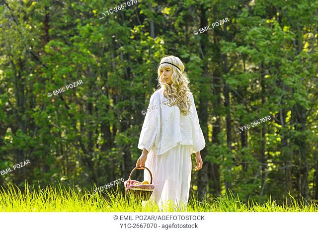 Teen girl in in nature with basket in hand