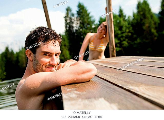 Couple swimming in a lake with a pier