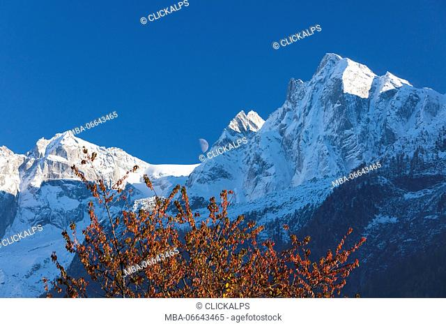 Blue sky and moon on the snowy peaks framed by colorful trees Soglio Bregaglia Valley canton of Graubünden Switzerland Europe