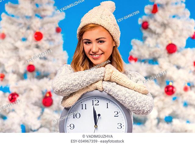 Young happy woman with a big alarm clock, during the celebration of Christmas, Christmas tree background