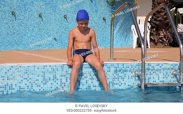 Boy is sitting on the edge of the pool wetting feet in water