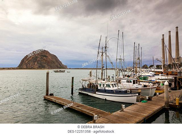 Boats tied up to the dock in Morro Bay, with Morro Rock in the background; California, United States of America