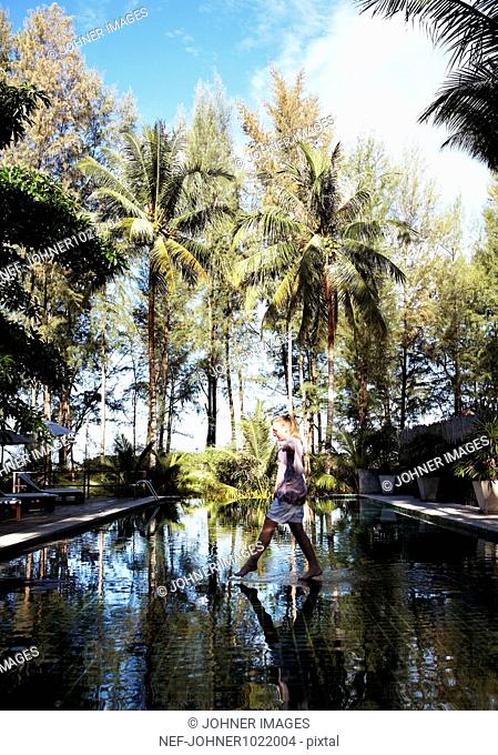 Thailand, woman crossing pool of water with palm trees reflecting