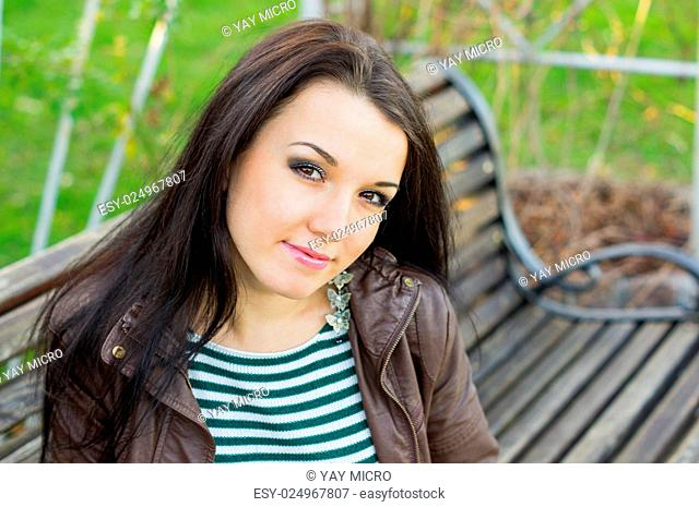 beautiful and sexy girl sitting on bench outdoors