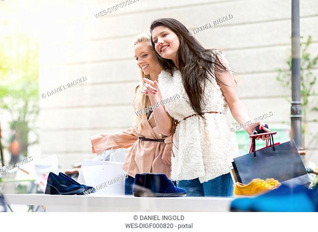 Two young women looking in shoe shop window