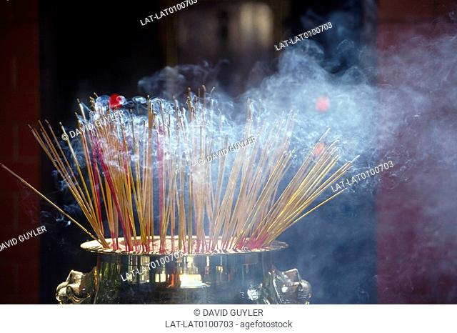 Wong Tai Sin temple. Interior. Incense burner. Large urn. Smouldering incense sticks. Smoke