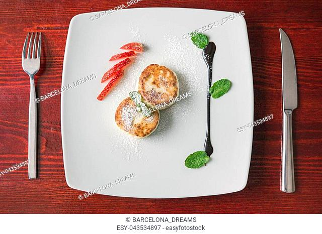 Breakfast dessert - pie with cottage cheese, green sweet sous and strawberry on white plate, top view