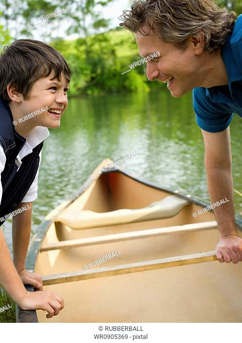 Profile of a man and his son bending forward over a canoe