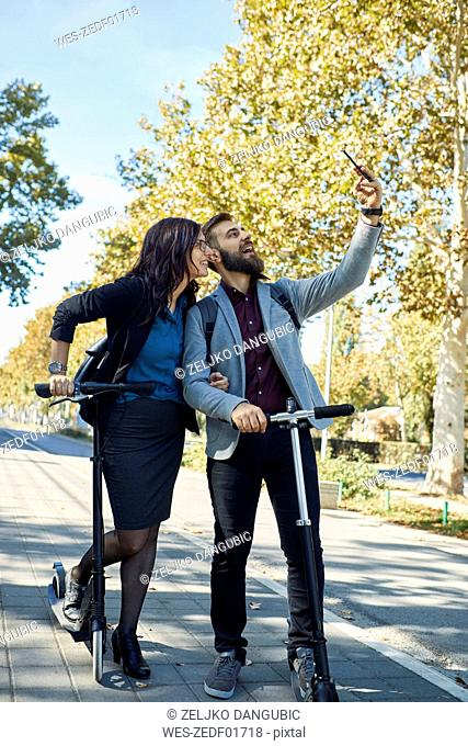 Happy business couple with scooters taking a selfie
