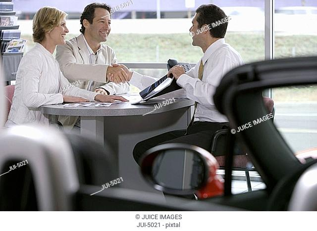 Couple sitting at desk in car showroom, salesman with brochure shaking hands with man, side view