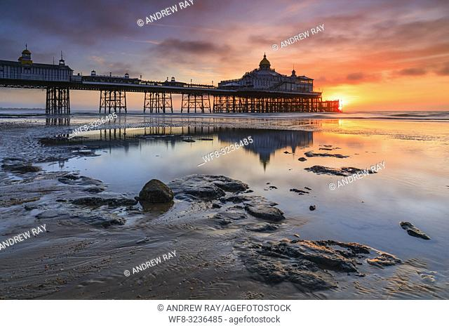 Sunrise and Eastbourne Pier reflected in a large pool of water on the adjacent beach. The image was captured from a low vantage point on a wind free morning in...