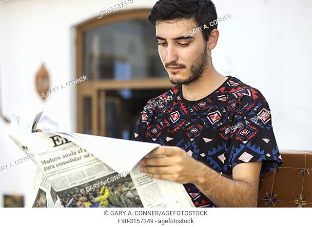 Young man reads newspaper at outdoor cafe, Salobreña, Spain