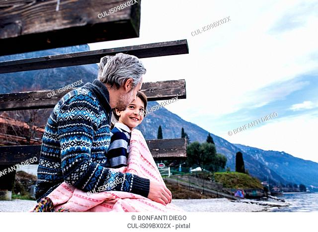 Boy and father wrapped in blanket on lakeside pier, side view, Lake Como, Onno, Lombardy, Italy
