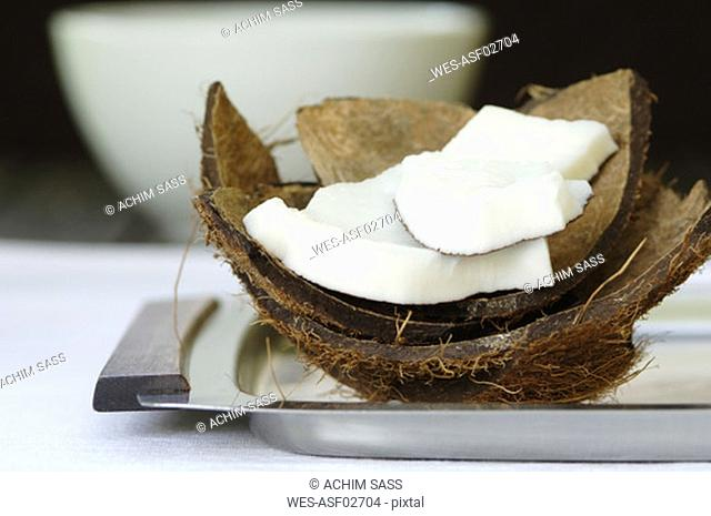 Fresh coconut slices, cup in background, close-up