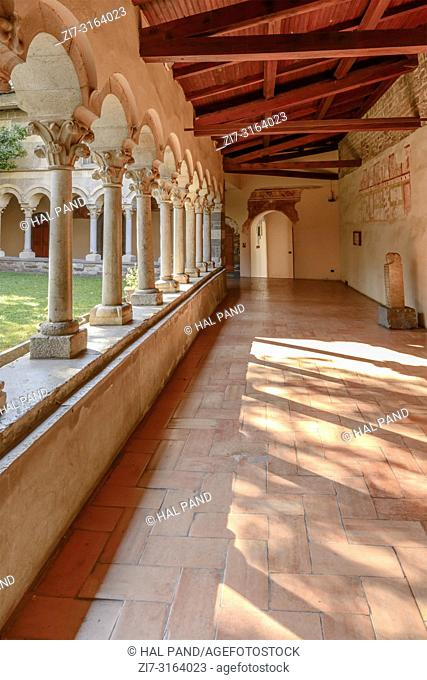 detail of light on floor through mullions and arches at Romanesque cloister of Abbey on shore of Lario lake, shot in bright fall light at Piona, Lecco, Italy