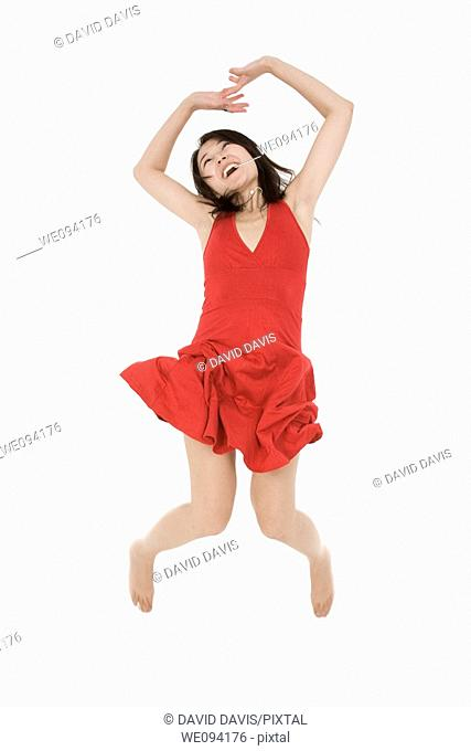 Beautiful Asain woman in a red sundress jumping on a white background