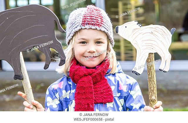 Portrait of smiling little girl holding two signs shaped like boars