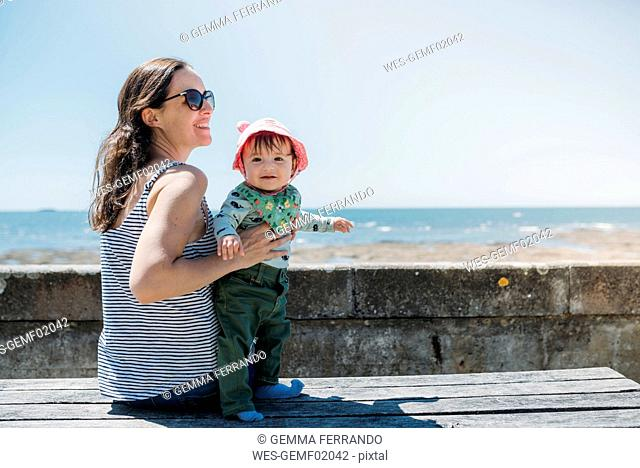 France, content mother and baby girl on a bench at beach promenade