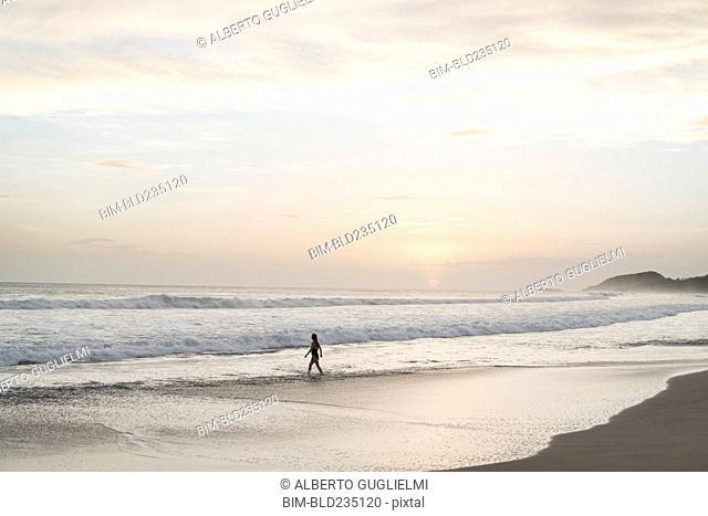 Caucasian woman walking on beach at sunset