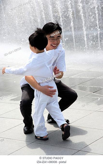 Mid adult man hugging his son near a fountain
