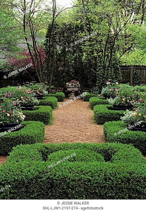 Gardens: Gravel pathway with large urns spilling flowers, set in sculpted shrubs